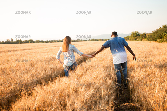 Couple holding hands while walking in field