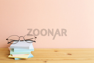 Glasses and stack of colorful memo pad, sticky notes on wooden desk. Pink background, copy space. Work and study place