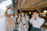 Caucasian women taking off a medical mask in a cafe
