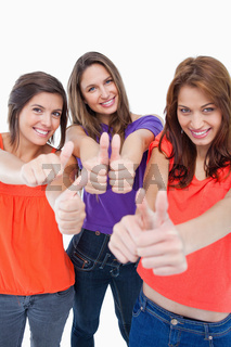 Three teenagers standing against a white background and showing their thumbs up