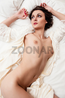 Beautiful naked brunette lying in bed