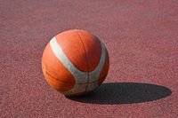 Orange basketball ball on red outdoors court