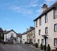 people walking in the street near the village square and shop in cartmel cumbria