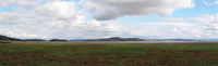 panoramic view of the coast at grange over sands in cumbria with grass covered wetland in the foregrounds and the north lakes area in the distance