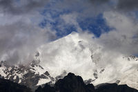 High snowy mountains with glacier, rocks and blue sky with dark fog before storm
