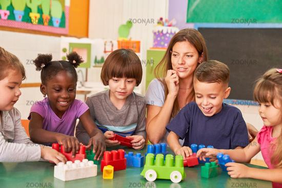 Gruppe Kinder spielt zusammen in Kita mit Erzieherin