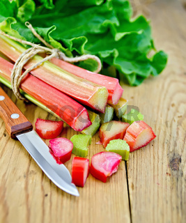 Rhubarb cut with a knife on a wooden board