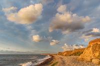 Wolken im Abendlicht über Ostseeküste mit Kiesstrand und Steilküste bei Dazendorf in der Nähe von Heiligenhafen