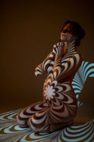 Nude pregnant woman in dark with ornamental shadows on body