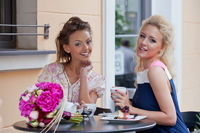 two beautiful young girls in summer outfit have lunch at the table in pavement cafe