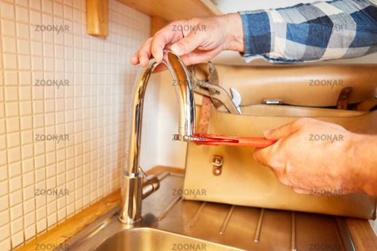 Klempner wechselt Mischdüse aus vom Wasserhahn