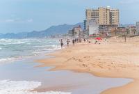 People walking along sand beach with high ocean waves in Daimus, Spain