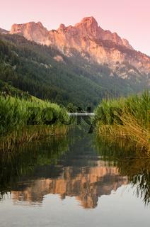 Berg im Abendrot mit Spiegelung im Wasser