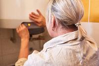 Heimwerkerin repariert den Durchlauferhitzer im Bad