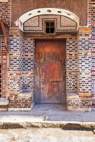 Wooden grunge decorated arched gate with inner small door on wall with black and red bricks