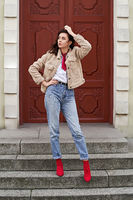 Young beautiful woman in red high heel shoes, blue denim jeans pants and teddy jacket coat posing on old red door background in European city