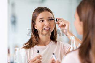 teenage girl applying mascara at bathroom