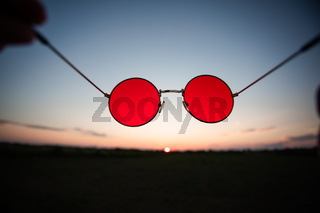 Pair of red glasses on sunset sky background