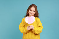 Portrait of cute little girl holding paper pink heart on stick and smiling to camera, sharing love.