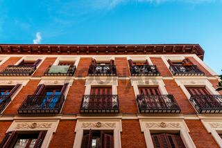 Low angle view of old recently renovated residential building against blue sky