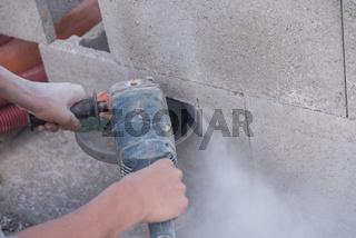 Belastung eines Bauarbeiters mit Winkelschleifer mit Staub und Lärm