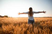 Peaceful woman wellcoming the rising sun in field