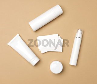 jar, bottle and empty white plastic tubes for cosmetics on a beige background. Packaging for cream, gel, serum, advertising and product promotion, mock up, top view