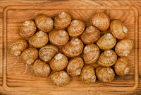 Two dozen of escargot snails on oak wood board