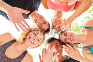 Gruppe junger Leute winkt fröhlich in die Kamera