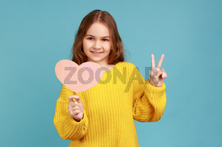 Portrait of little girl holding paper pink heart on stick and smiling to camera, showing v sign.