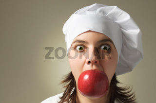 Chef woman with a red apple in her mouth