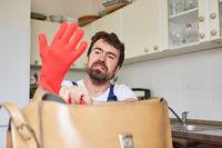 Heimwerker zieht sich Gummihandschuhe an