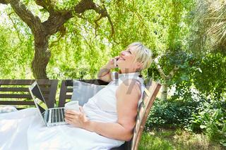 Ältere Frau als Freelancer telefoniert im Garten