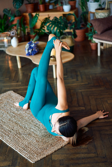 Top view of young sporty woman practicing stretching exercise doing one armed swastikasana yoga pose