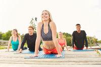 Leute machen Dehnungsübung im Yoga Workshop