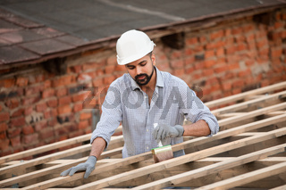 The young builder works on an unfinished roof