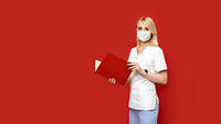 Confident female doctor wearing protective face mask standing on red background with notebook or medical book in her hands. Young woman intern in medical clothes posing.