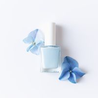 Blue petals with nail polish in transparent glass bottle, white background