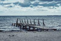 old damaged wooden pier on beach