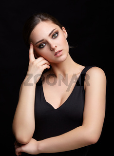 Beauty portrait of young woman. Brunette girl with evening female makeup and black dress
