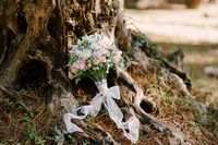 bridal bouquet of white and pink roses, wild berries, eustoma with white lace ribbons on the ground near tree trunk