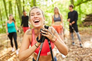 Lachende junge Frau beim Nordic Walking Kurs