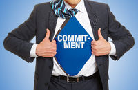 Mann in Anzug zeigt Schriftzug Commitment
