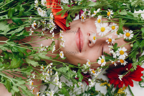 Young man model with flowers. Beauty boy portrait.