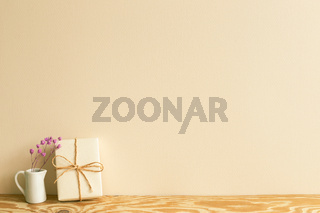 Gift box and pink dry flowers on wooden table. beige wall background