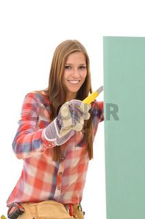 Frau schneidet eine gruene Gipskartonplatte