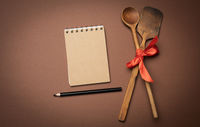 old spoon and spatula tied with red ribbon on a brown background, top view, copy space