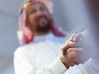 Business meeting with arab man and shaking each other hands in greetings and introduction discussing and planning within modern office in background