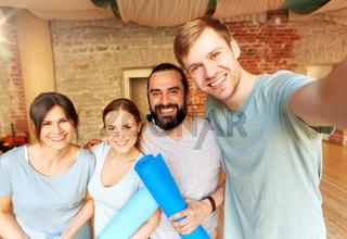happy friends at yoga studio or gym taking selfie