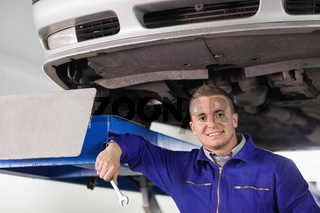 Mechanic holding a spanner below a car